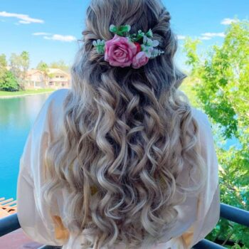 Beautiful long blonde hair with pink flower for bride overlooking lake at The Salon at Lakeside
