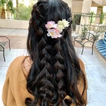 Long black hair braided with flowers for bride at The Salon at Lakeside